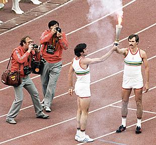 Виктор Санеев передает олимпийский факел Сергею Белову